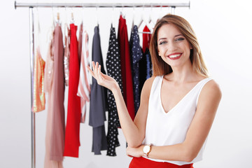 Wall Mural - Beautiful young stylist near rack with designer clothes on white background