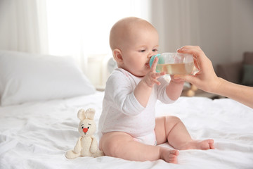 Lovely mother giving her baby drink from bottle on bed in room