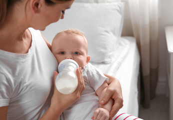 Lovely mother holding and feeding her baby from bottle on bed. Space for text
