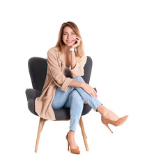 Fototapeta Young woman sitting in armchair on white background obraz