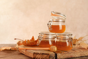 Dipper and jars with honey on table against color background. Space for text
