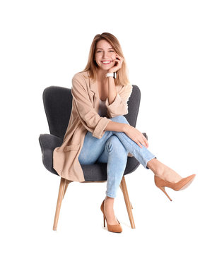 Young woman sitting in armchair on white background