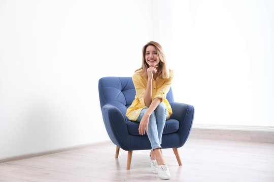 Young woman sitting in armchair at home
