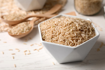 Uncooked brown rice in bowl on table