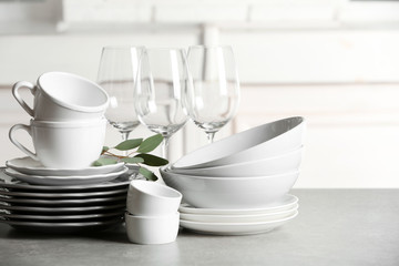 Set of clean dishes on table against blurred background