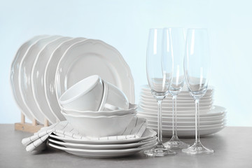 Set of clean dishes on table against light background