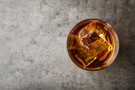Golden whiskey in glass with ice cubes on table, top view. Space for text