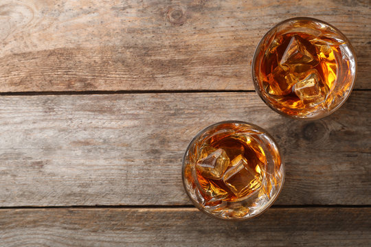 Golden whiskey in glasses with ice cubes on wooden table, top view. Space for text