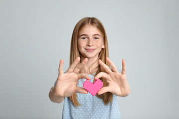 Pretty teenage girl with decorative heart on color background