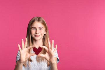Pretty teenage girl with decorative heart on color background. Space for text