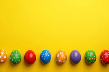 Decorated Easter eggs and space for text on color background, top view