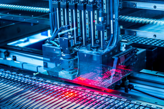 Electronic circuit under surface-mounting machine. Shot in blue toning filter. Surface-mount technology as a producing of electronic circuits. Components placed onto the surface of printed elements.