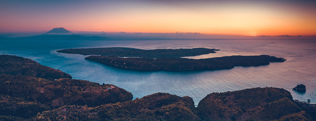 Sunset panorama rview of Indonesia shoreline and ocean. Aerial drone shot of Asian wild nature. Breathtaking landscape. Sunset over the Indonesian land and calm ocean. Bright colorful sky.