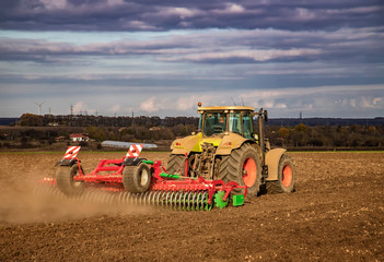 The tractor prepares the ground for sowing and cultivation. Agriculture and agronomy concept.