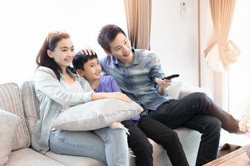 Happy family time. Mother, Father and son relaxing in living room at home.