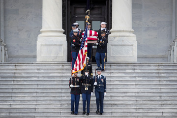 The flag-draped casket of former President George H. W. Bush is carried by a joint services military honor guard down the steps of the U.S. Capitol,