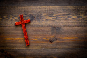 Funeral concept. Wooden cross on dark wooden background top view copy space