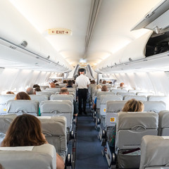 Interior of commercial airplane with unrecognizable passengers on their seats during flight. Steward in blue white uniform walking the aisle of commercial airplane.