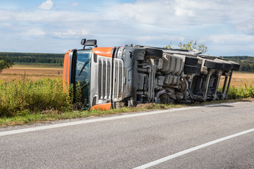 Overturned truck in field next to road, chassis visible