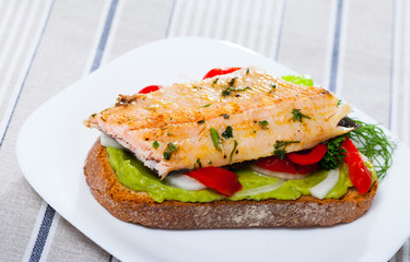 Tasty piece of bread with fried trout fillet