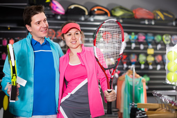 female with male are standing in sportwear with new racket for padel and tennis in the speciality store