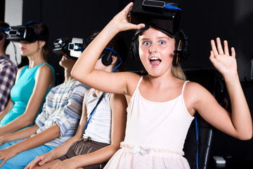 Young girl is excited by watching the video in VR glasses