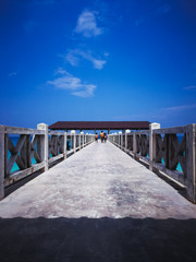Wooden jetty in the noon under clear blue skies with people walking.