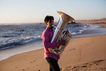 Young musician playing the tuba on the sea coast.
