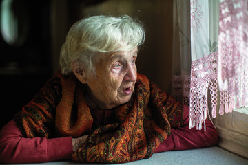 Elderly woman sitting at the table.
