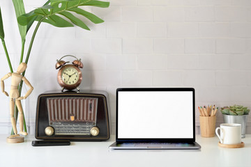 Loft workspace with vintage radio and blank screen laptop
