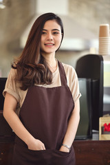 Portrait of attractive Asian barista woman standing at front of coffee bar counter.
