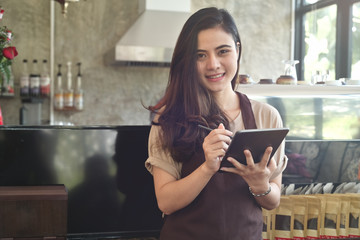 Asian women Barista smiling and using tablet for take order in coffee shop counter