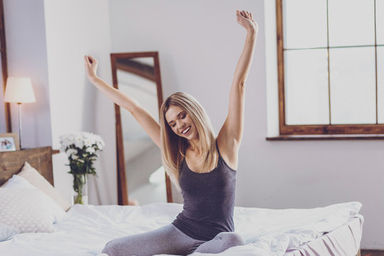 Pretty young woman stretching herself on bed