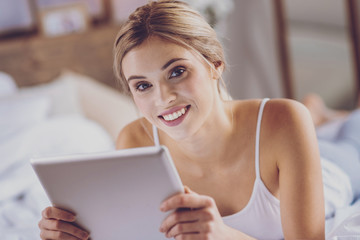 Close up of beautiful young woman using tablet on bed