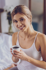 Close up of cheerful young woman posing with coffee