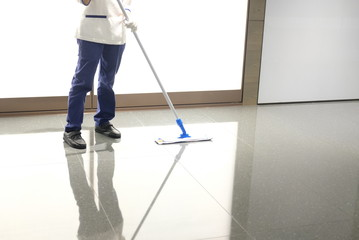 Uniformed cleaner wipes the floor using a mop