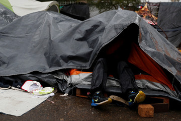 A migrant, part of a caravan of thousands from Central America trying to reach the United States, shelters from the rain as he stays on the street in Tijuana