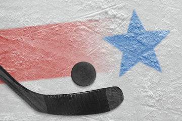 An image of a red line with a blue star on ice and a stick with a puck