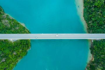海を渡る橋の上を一台の車が走っている風景