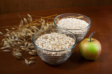 Oat ears stems and oat flakes and green apple in a bowl on a dark brown wood background. oat flakes big and small size grind. oatmeal flakes coarse. large-sized flakes. Useful fiber-rich product.