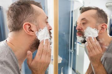 Man applying shaving cream on beard