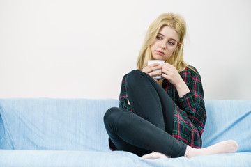 Sad lonely woman sitting on couch with mug