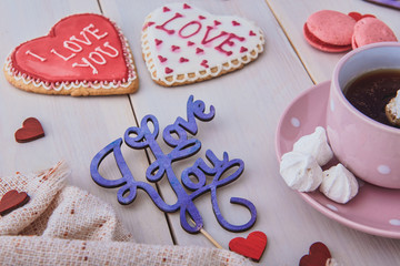 Valentine's day breakfast. Delicious coffee and cookies on a white wooden table. Start a romantic and lovely day. Top view.