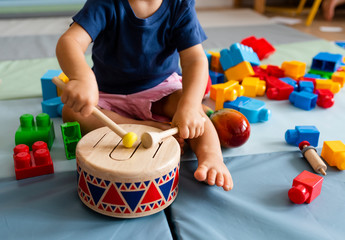 Obraz Little boy having fun and playing wooden toy drum - fototapety do salonu