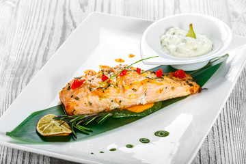 Baked salmon with cheese sauce, rosemary and lemon on wooden background. Hot fish dish. Top view