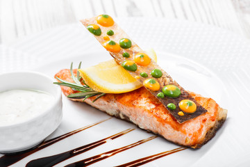Baked salmon with cheese sauce, rosemary and lemon on wooden background close up. Hot fish dish