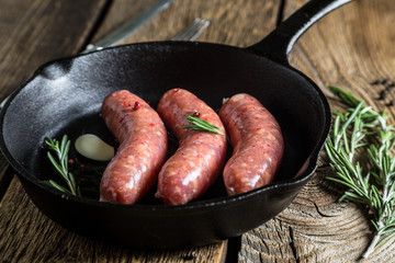 Roasting sausages in a pan with herbs and spices