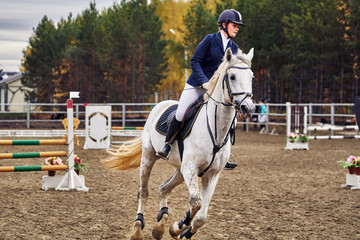 Young woman jockey in white blue dress and black boots, takes part in equestrian competitions.