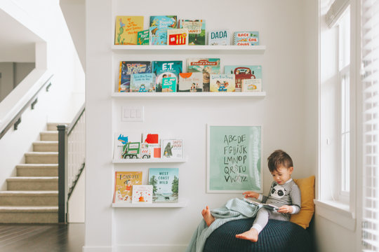 A little boy reading in a reading corner of his play room.