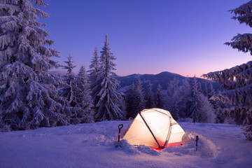 Tourist tent in winter forest at the night